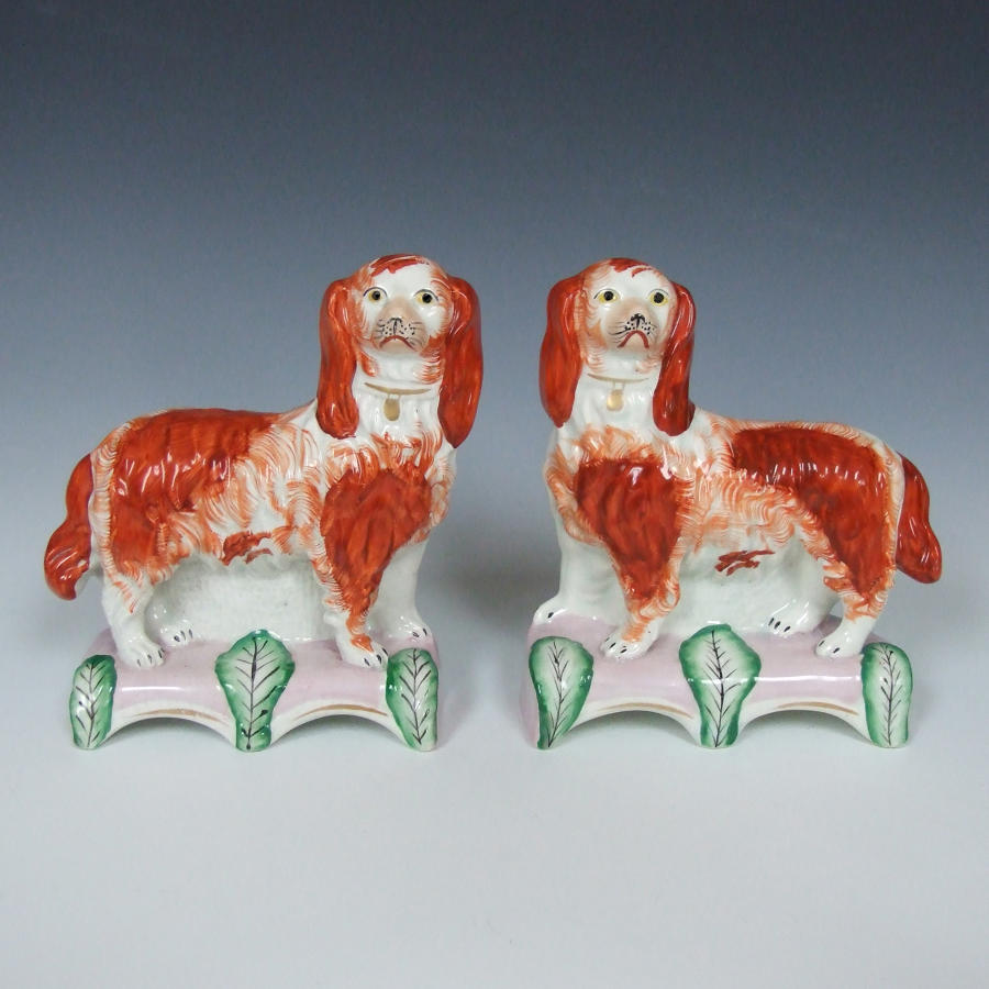 Pair Staffordshire spaniels on pink cushions