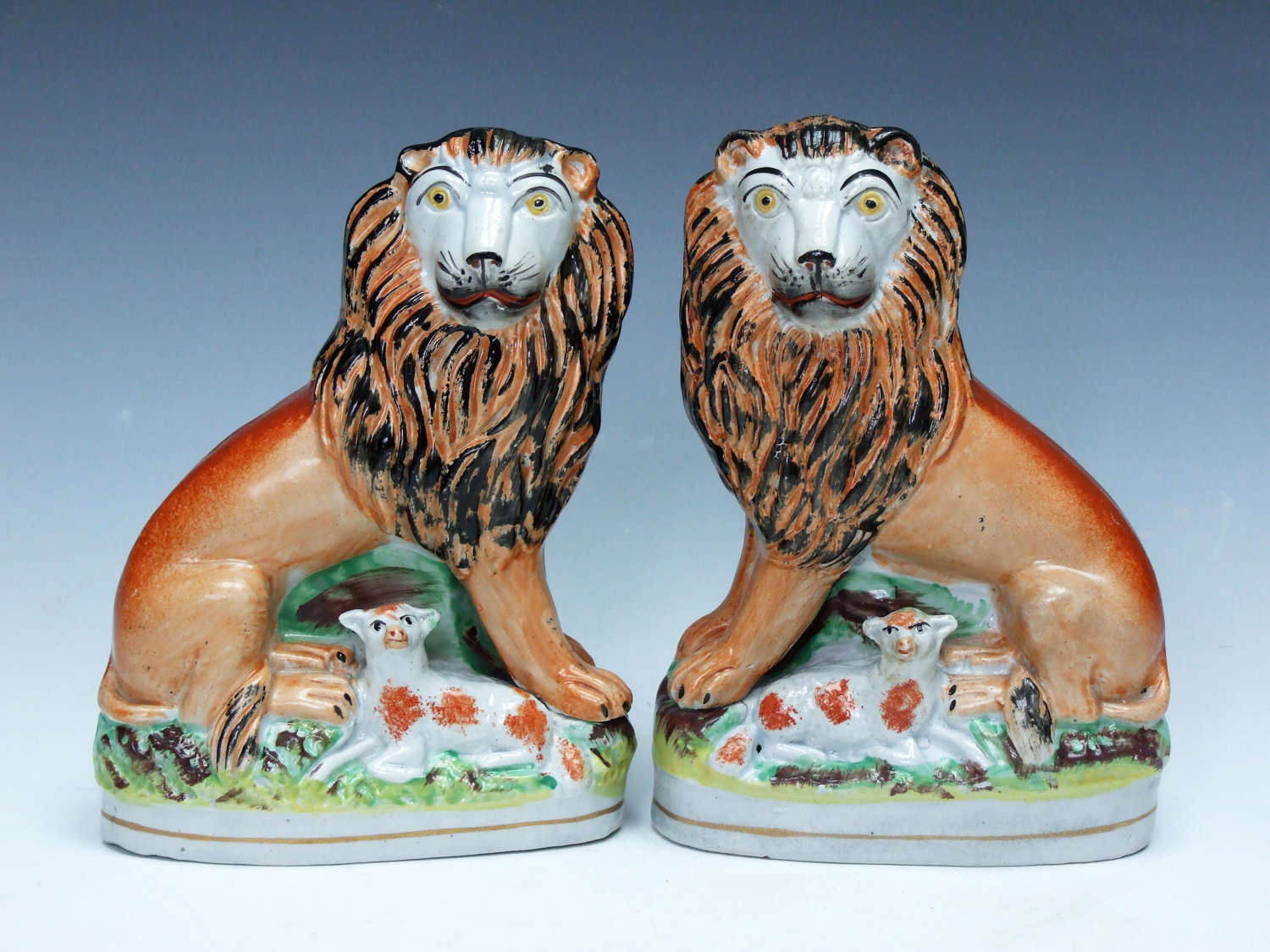 An extremely rare & charming pair of Staffordshire lion & lamb figures