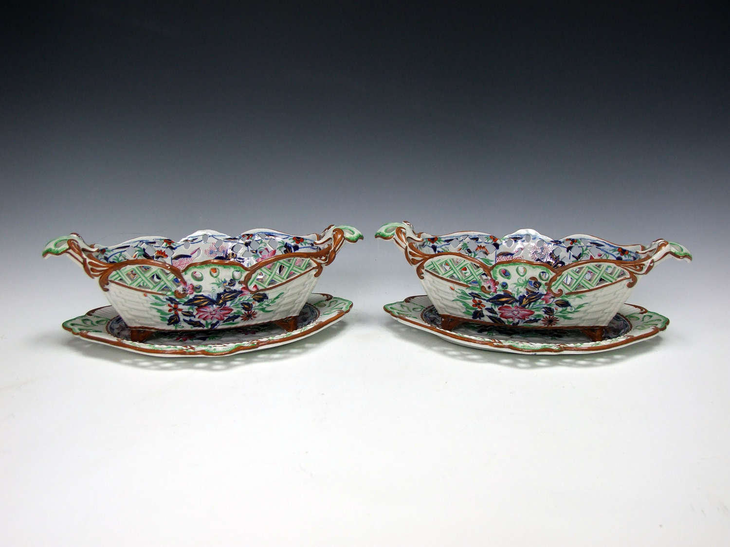 A beautiful mint condition pair of Spode chestnut baskets and stands.